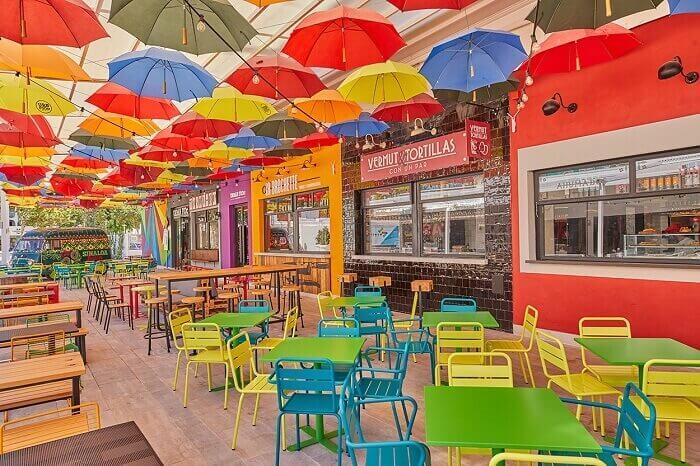 diseño de local con paraguas en el techo de colores, mesas y sillas de color verde amarillo y azul, realizado por arquitecto interiorista en Palma nuustudio